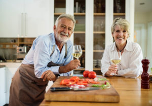 This is a photo of a couple in their kitchen enjoying a glass of white wine