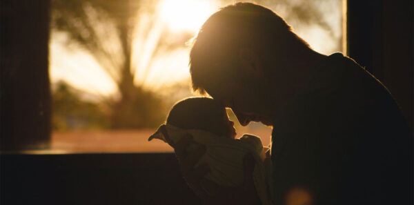Beneficiaries Special Needs - photo of man holding a newborn infant